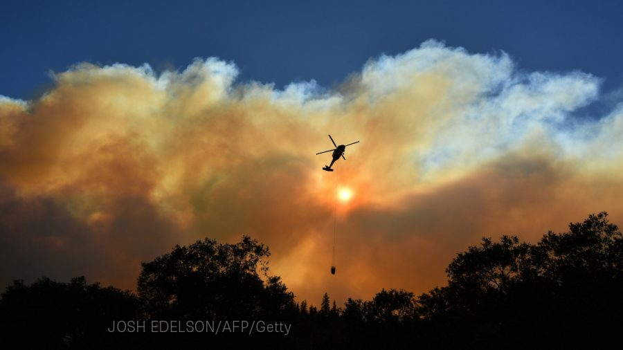 A helicopter passes by the sun as it makes a water drop in the Feather River Canyon, east of Paradise, California on November 11, 2018. (Photo by Josh Edelson / AFP)        (Photo credit should read JOSH EDELSON/AFP/Getty Images)
